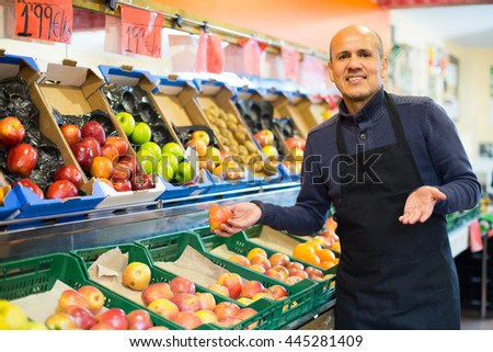Portrait of positive smiling male seller offering seasonal fruits at market