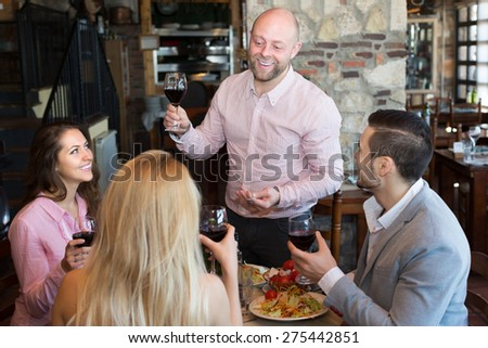 Portrait of positive young adults having dinner in restaurant - stock photo