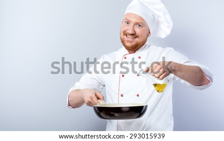 Portrait of positive young male chef in white uniform. Head-cook cheerfully smiling, holding pan and pouring olive oil in it. Standing against grey background