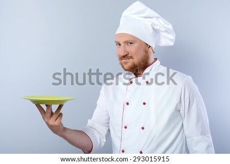 Portrait of positive young male chef in white uniform. Head-cook holding plate and looking at camera. Standing against grey background - stock photo