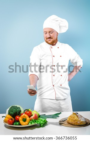 Portrait of positive young male chef in white uniform. Head-cook making photo of food by using phone. Standing against grey background near table with fresh food