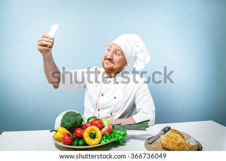 Portrait of positive young male chef in white uniform. Head-cook making photo of himself by using phone. Sitting against grey background near table with fresh food - stock photo