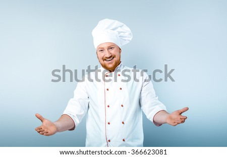Portrait of positive young male chef in white uniform. Head-cook smiling and stretching out his hands to camera. Standing against grey background - stock photo