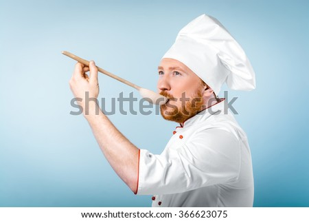 Portrait of positive young male chef in white uniform. Head-cook tasting food from wooden spoon and standing against grey background - stock photo