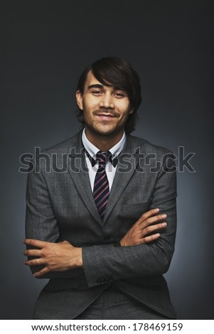 Portrait of positive young man wearing suit sitting with his arms crossed against black background. Handsome businessman with folded hands. Mixed race model. - stock photo