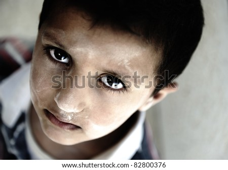 Portrait of poverty, little boy with sad eyes - stock photo