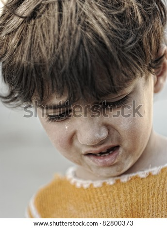 Portrait of poverty, little boy with sad look - stock photo