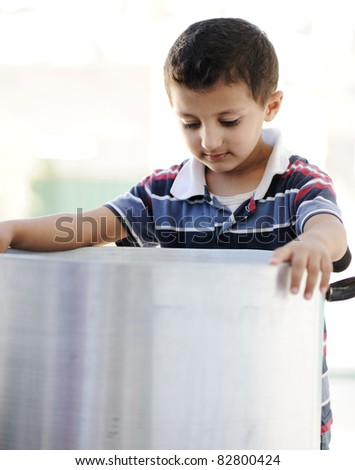 Portrait of poverty, little poor boy on food pot - stock photo