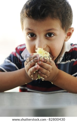 Portrait of poverty, little poor boy on food pot eating rice - stock photo