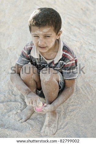 Portrait of poverty, little poor dirty boy in sand - stock photo