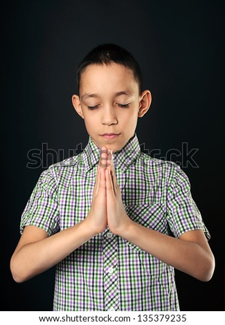 portrait of praying boy wearing shirt with closed eyes over black