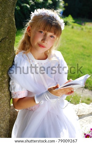 portrait of praying girl in white dress and  wreath,going to the first holy communion posing in park - stock photo