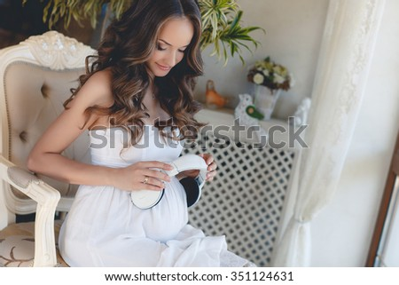 Portrait of pregnant woman sitting on sofa at home and listening music in headphones. Pregnant girl listens to music at home. We love music. Beautiful pregnant woman holding headphones - stock photo