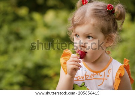 Portrait of preschool age girl with strawberry - stock photo