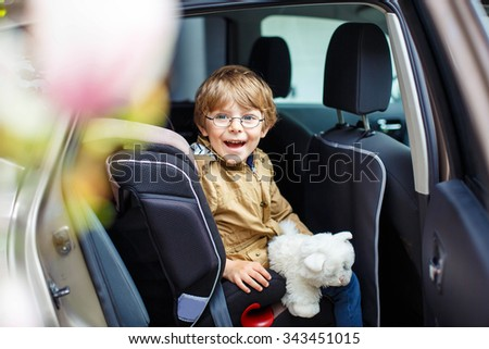 Portrait of preschool little kid boy with glasses sitting in car. Child in safety car seat with belt and toy. Safe travel with kids and traffic laws concept. - stock photo