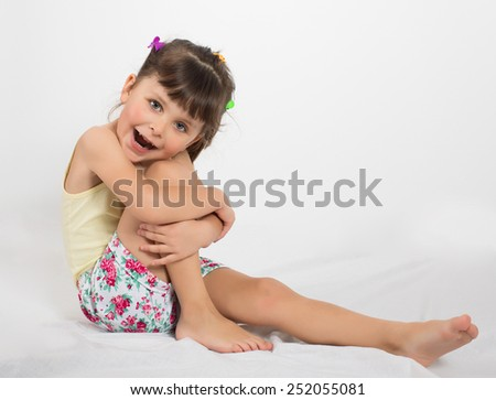 Portrait of preschooler girl in shorts and tank top. Charming child posing on white background indoors. Studio shot - stock photo