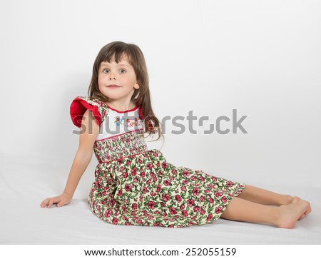 Portrait of preschooler girl in summer dress. Charming child posing on white background indoors. Studio shot - stock photo
