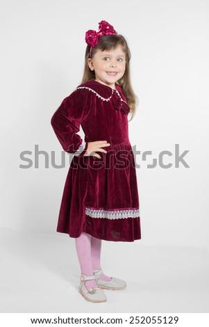 Portrait of preschooler girl in velvet dress. Charming child posing on white background indoors. Studio shot - stock photo