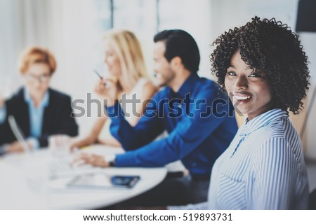 Portrait of pretty african american business woman with afro smiling at the camera.Coworking team in brainstorming process on background in meeting room. Horizontal,blurred