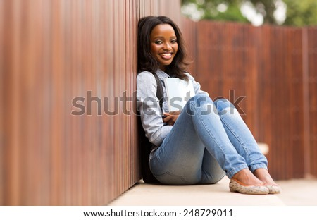 portrait of pretty african college girl sitting on the floor - stock photo