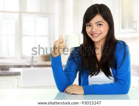 portrait of Pretty asian woman having a glass of tea while breakfast - stock photo