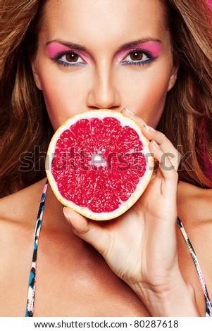 portrait of pretty bikini woman with grapefruit against pink background - stock photo