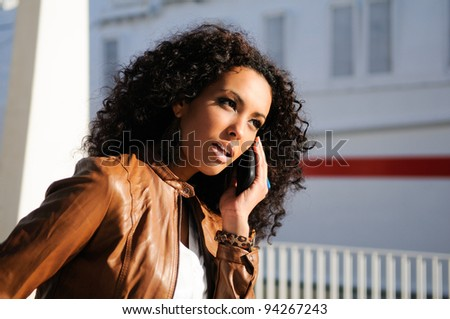 Portrait of pretty black woman in urban background talking on phone - stock photo