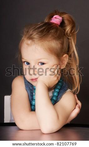 Portrait of pretty blond blue-eyed little girl, studio shot - stock photo