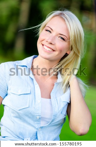 Portrait of pretty blond female student in the summer park - stock photo