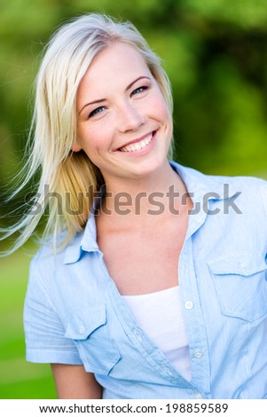 Portrait of pretty blond woman in the summer park - stock photo