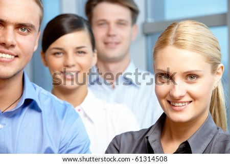 Portrait of pretty blonde looking at camera with partners on background - stock photo