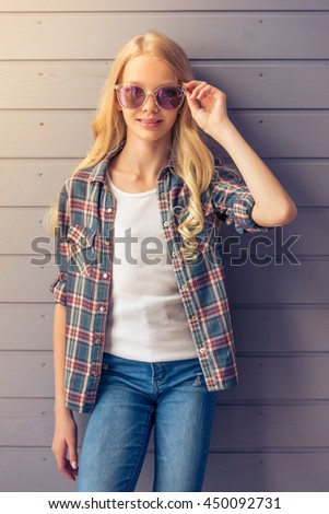 Portrait of pretty blonde teenage girl in casual clothes and sun glasses looking at camera and smiling while standing against gray wall - stock photo