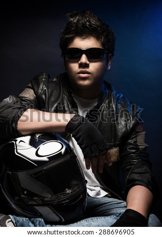 Portrait of pretty boy wearing stylish leather jacket, sunglasses and holding helmet posing in the studio over blue background, biker's fashion