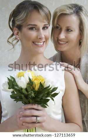 Portrait of pretty bride holding bouquet while standing with mother - stock photo