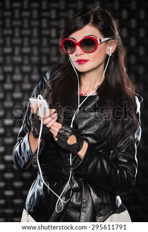 Portrait of pretty brunette in black jacket posing with mobile phone and headsets - stock photo