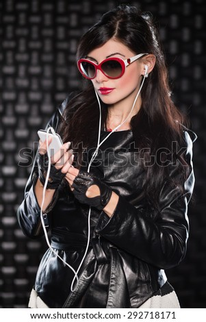 Portrait of pretty brunette in red sunglasses posing with mobile phone and headsets - stock photo