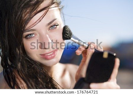 Portrait of pretty brunette posing with a brush for makeup - stock photo