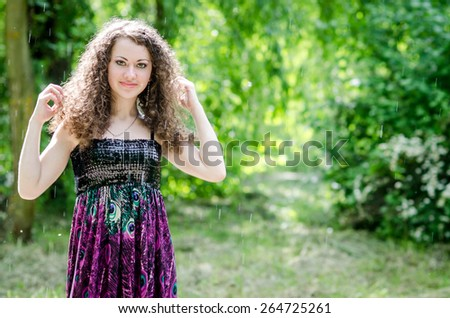 Portrait of pretty brunette woman at summer green park - stock photo