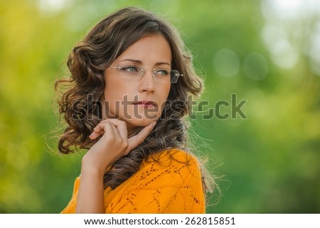 Portrait of pretty brunette young woman wearing eyeglasses and yellow blouse, standing at summer green park. - stock photo