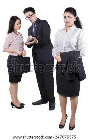 Portrait of pretty business leader looking at the camera with two employee on the back - stock photo