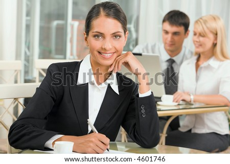 Portrait of pretty business woman in the cafe on the background of two business people talking
