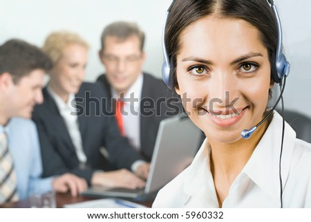 Portrait of pretty business woman with her team on the background - stock photo