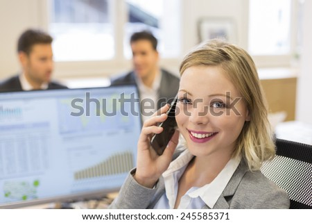 Portrait of pretty businesswoman on mobile phone in modern office. Looking camera - stock photo