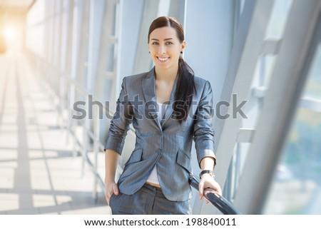 Portrait of pretty businesswoman on the modern background - stock photo