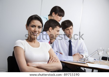 Portrait of pretty businesswoman smiling while colleagues working in background - stock photo