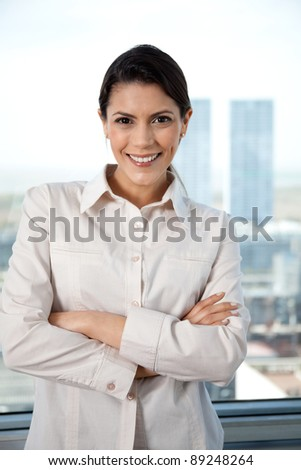 Portrait of pretty businesswoman with arms crossed - stock photo