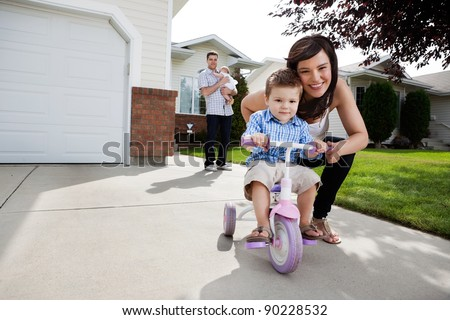 Portrait of pretty cheerful mother teaching her son to ride tricycle