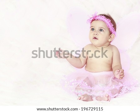 Portrait of pretty child girl in butterfly costume on pink background - stock photo