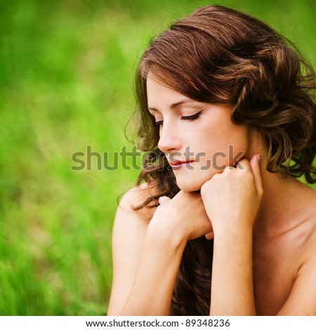 Portrait of pretty dark-haired curly woman sitting on grass at summer green park. - stock photo