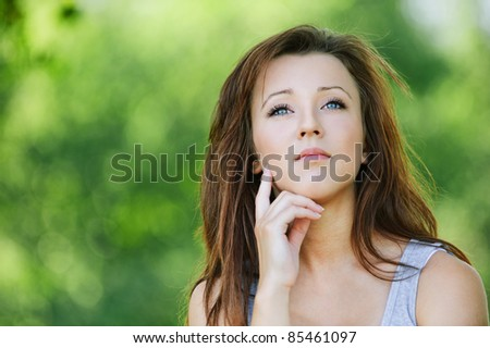 Portrait of pretty dark-haired pensive girl at summer green park. - stock photo